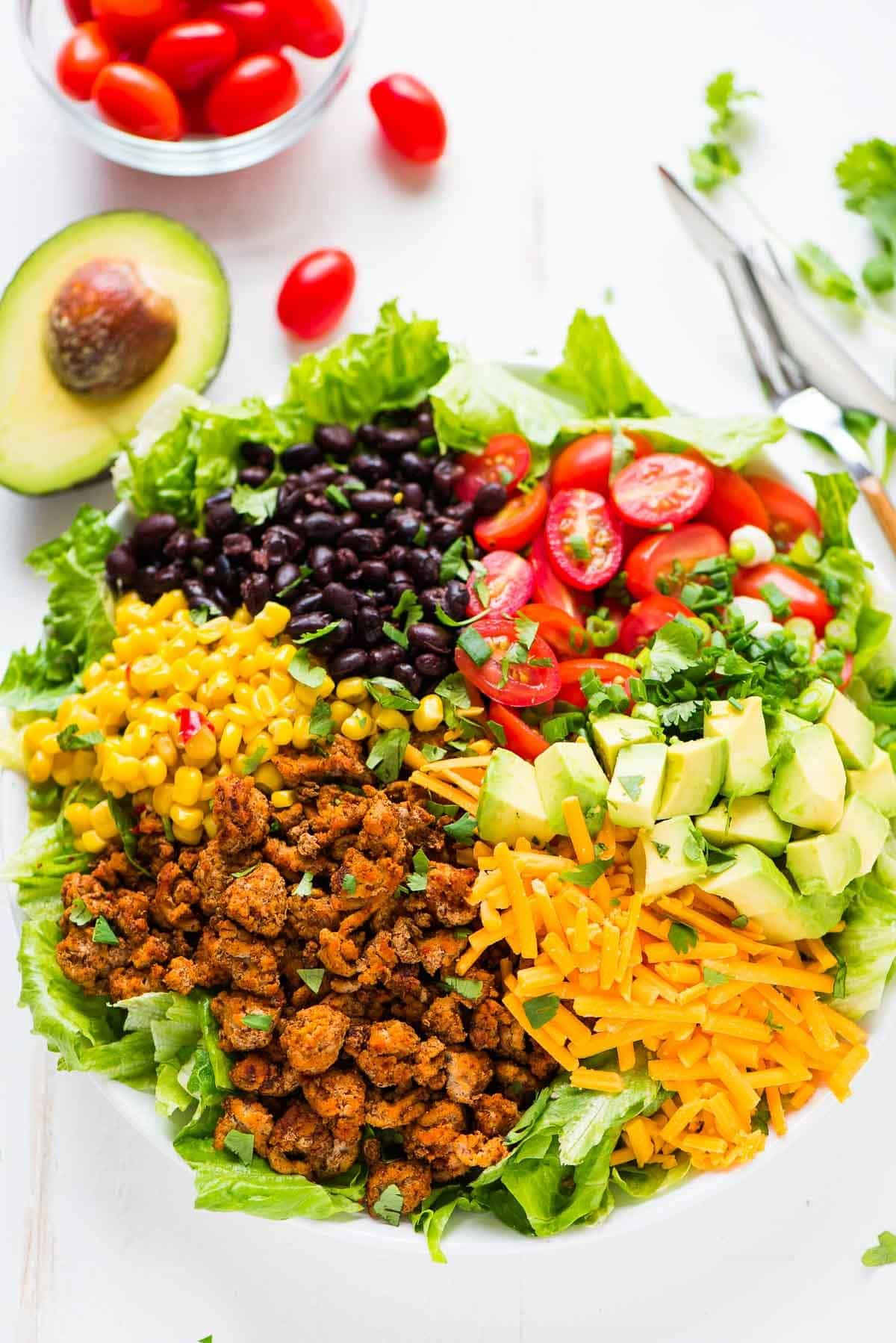 Ingredients for making skinny taco salad like ground turkey, tomatoes, avocado, black beans, corn, and cheese