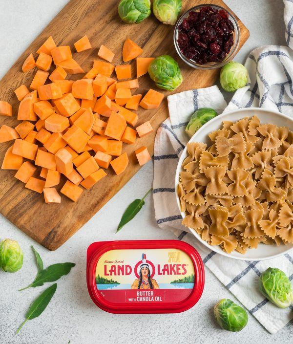 Healthy ingredients like sweet potato, Brussels sprouts, whole wheat pasta, butter, and cranberries for making sweet potato pasta with Brussels sprouts