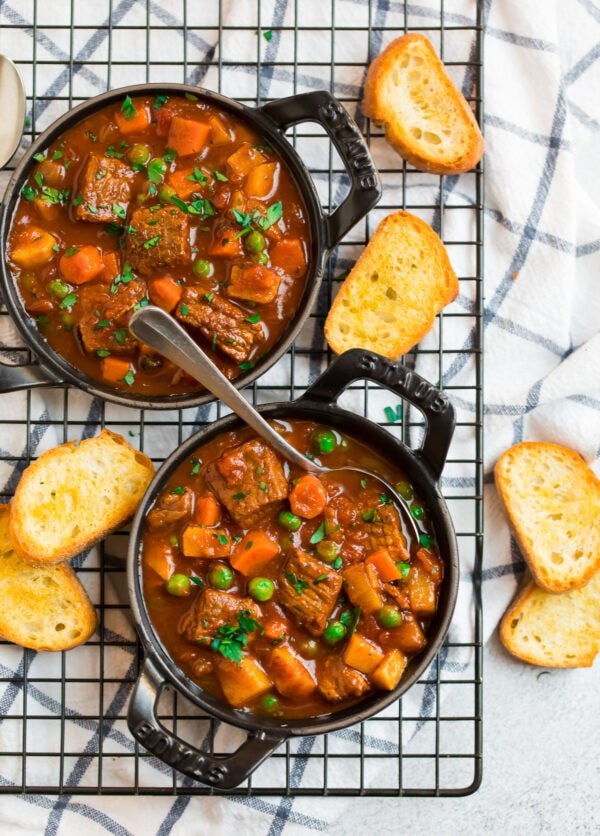 Easy crockpot vegetable beef soup served in bowls with fresh parsley and bread