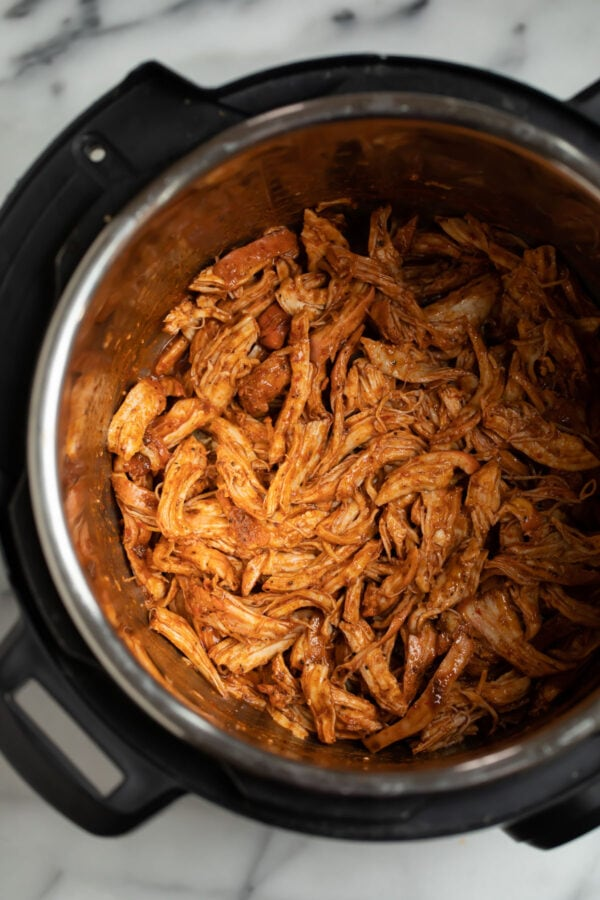 An Instant Pot with shredded chicken for making enchiladas