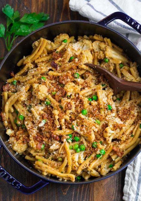 Healthy cauliflower pasta in a skillet topped with bacon breadcrumbs