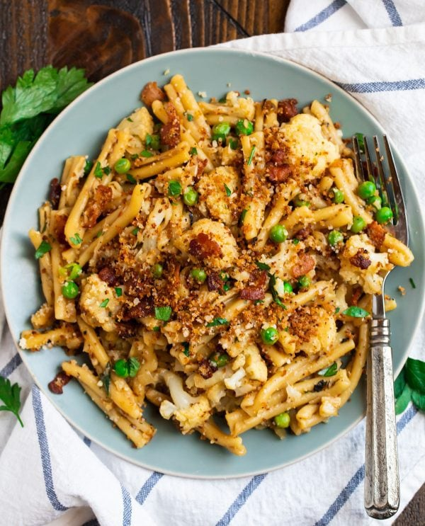 Healthy cauliflower pasta served on a plate with peas and bacon breadcrumbs