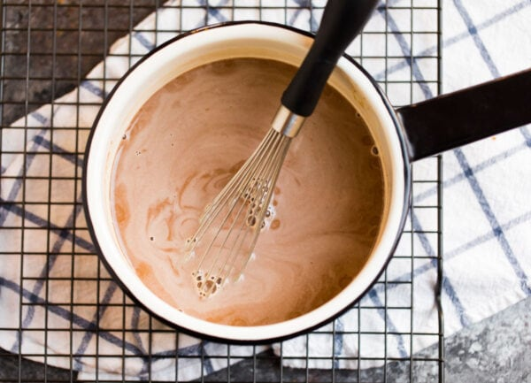 Healthy hot chocolate with almond milk in a mixing bowl
