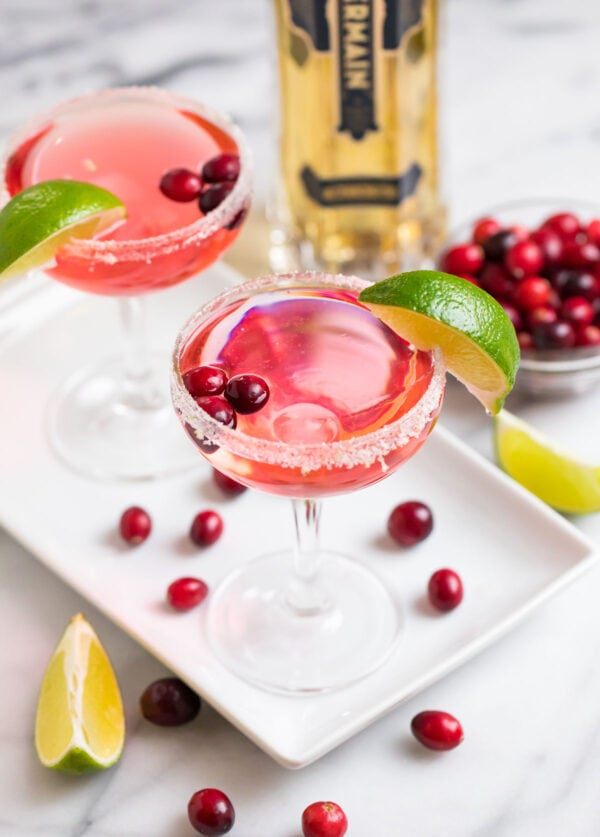 Cranberry St. Germain cocktails with sugar rims and lime wedges
