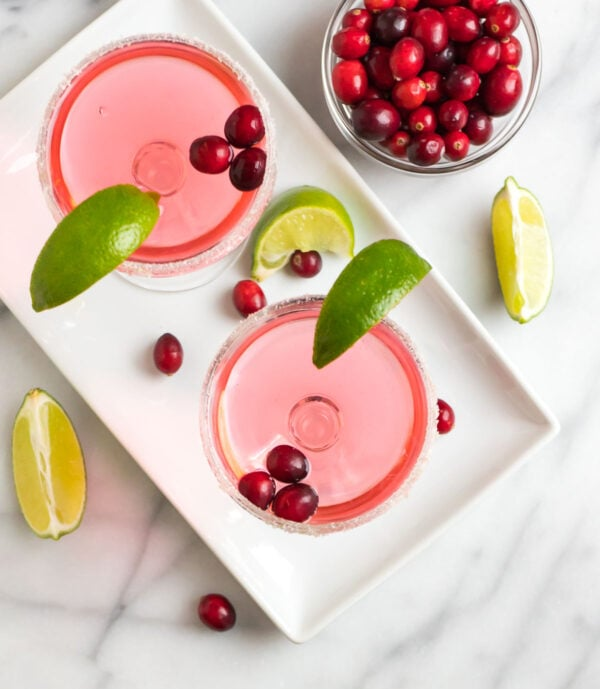 A delicious and festive holiday cocktail served with lime wedges and cranberries