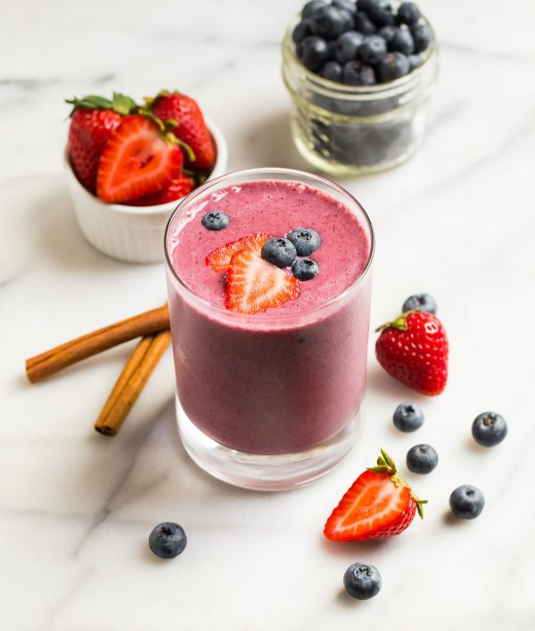 Good for you strawberry blueberry smoothie in a glass with cinnamon