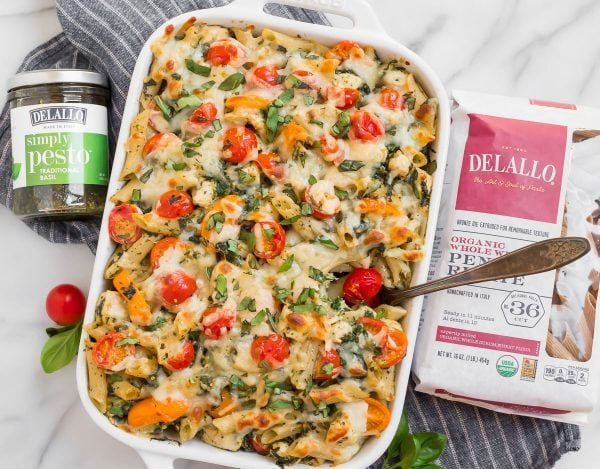 Creamy and tasty chicken pesto pasta recipe in a baking dish with tomatoes