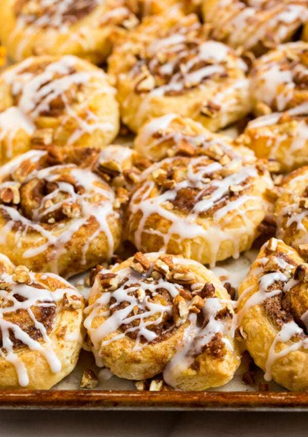 Easy puff pastry cinnamon rolls topped with glaze and toasted pecans