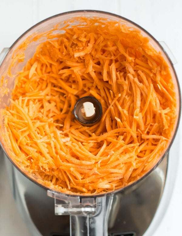 Shredded sweet potatoes in a food processor for making hash browns