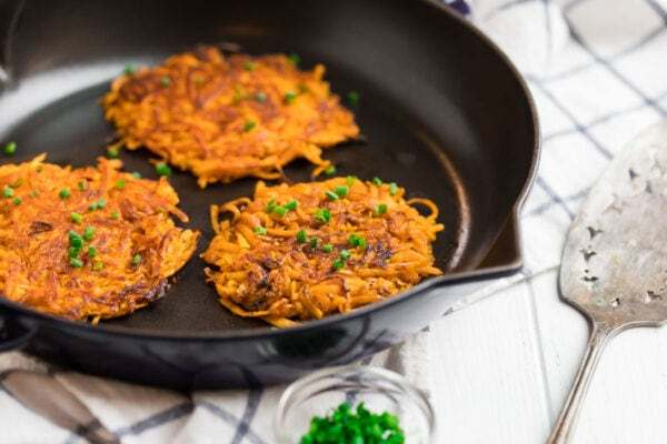 Healthy sweet potato hash browns in a skillet with chives