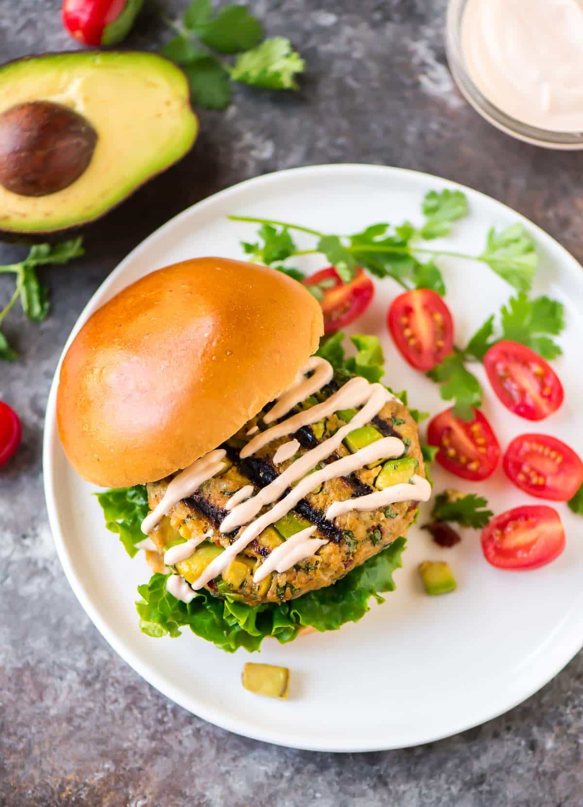 Chicken Avocado Burger with Chipotle Yogurt Sauce. Easy with SO MUCH FLAVOR. Big chunks of avocado mixed with chicken or turkey, cilantro and chipotle peppers. Healthy and delicious! Recipe at wellplated.com | @wellplated