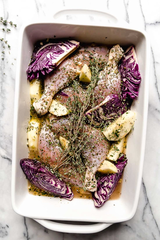 Cider-marinated chicken, red cabbage and apples in a baking dish.