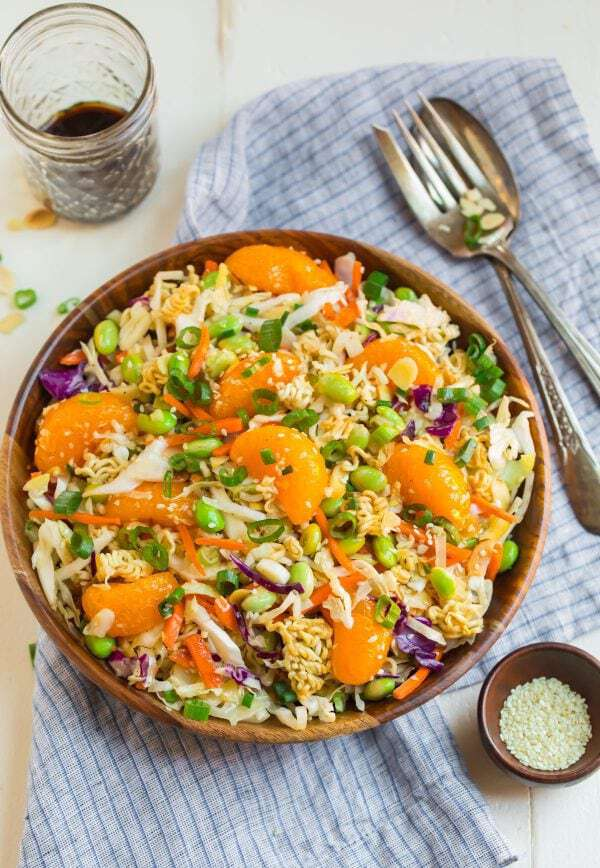 Healthy and crunchy Ramen Noodle Salad made with cabbage coleslaw in a wooden bowl, topped with ramen noodles and mandarin oranges
