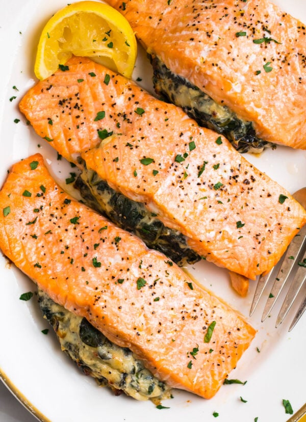 Spinach stuffed salmon on a platter with fresh herbs