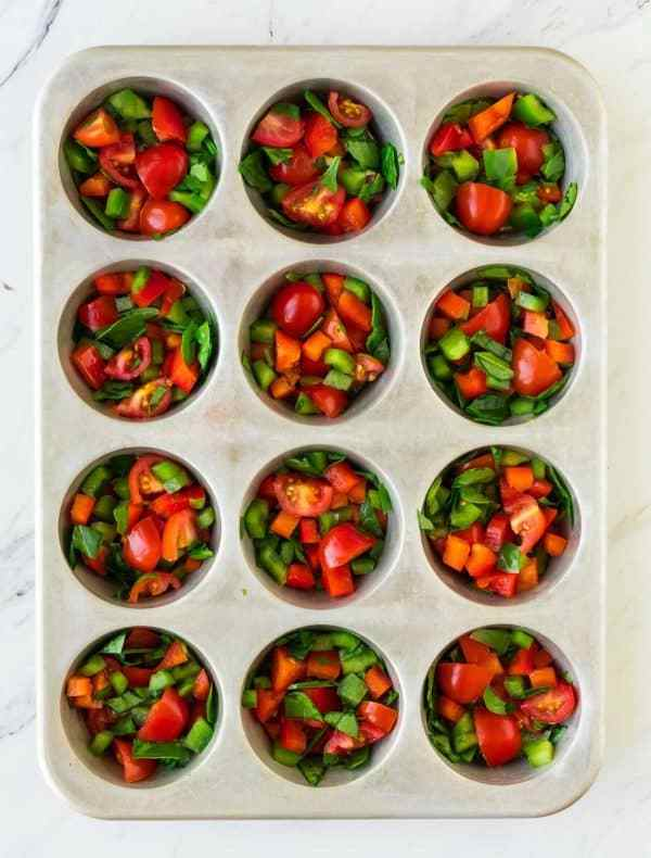 A muffin pan filled with chopped vegetables