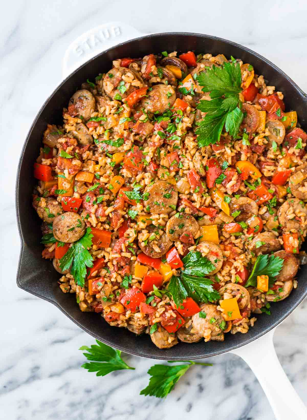A pan filled with sausage, rice, bell peppers, and fresh herbs