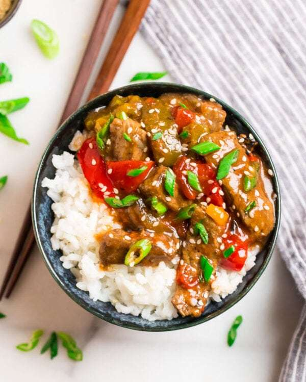 Crock pot pepper steak served in a bowl with white rice and peppers