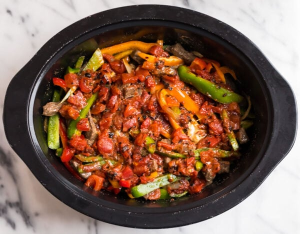 A slow cooker filled with peppers, tomato, onions, and beef for making a stir fry