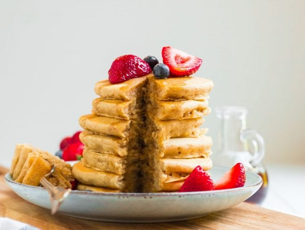 A stack of pancakes with a bite taken out and fruit on top