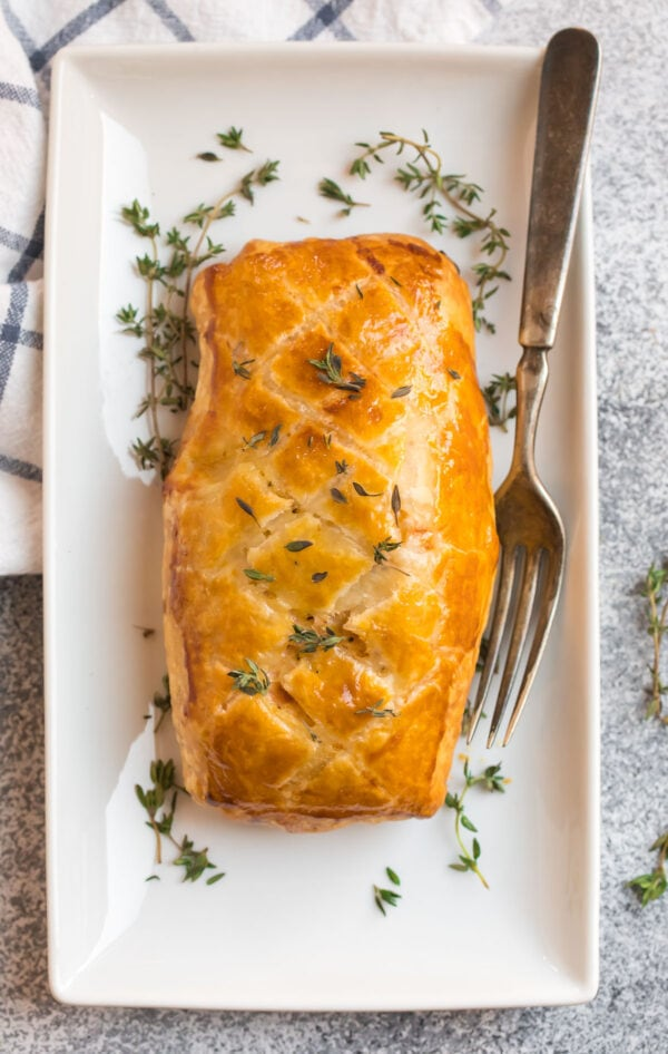A white plate with delicious salmon Wellington and fresh herbs