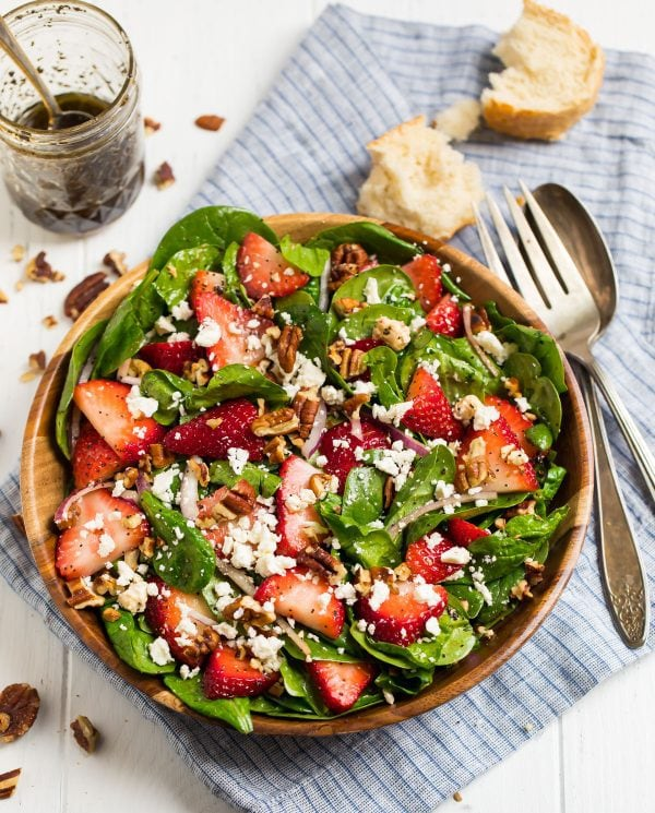 A bowl of strawberry spinach salad with chopped pecans, cheese, and poppy seed dressing