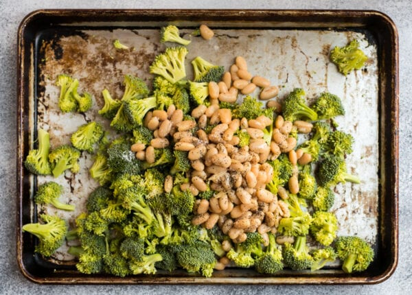 A baking sheet with broccoli, white beans, and spices