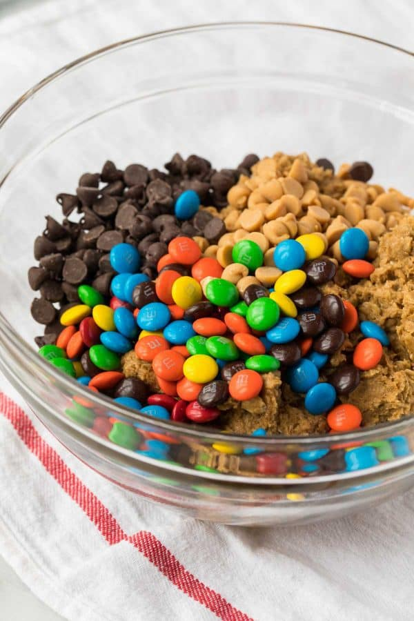 A glass bowl with chocolate chips, chocolate candies, peanut butter chips, and cookie dough