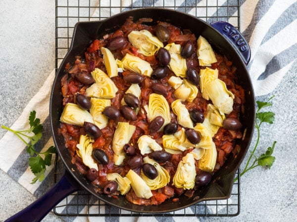A skillet with tomatoes, olives, and artichokes