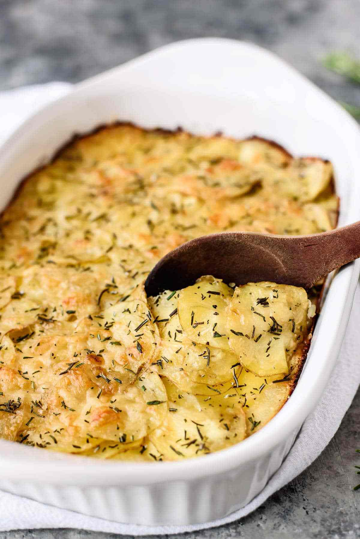 Homemade scalloped potatoes in a baking dish with a wooden spoon