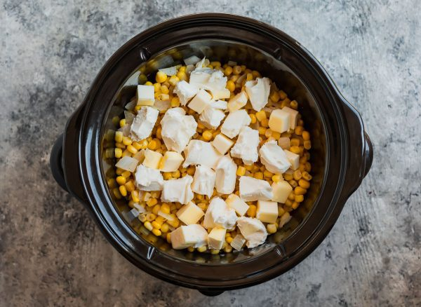 Cubes of butter and cream cheese in a slow cooker with corn