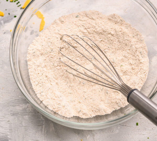 A whisk in a mixing bowl with dry ingredients