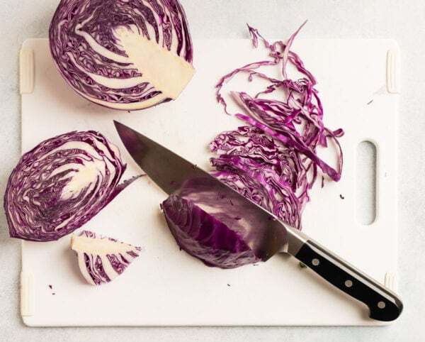 A head of red cabbage being cut into strips on a cutting board