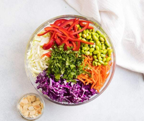 Bell pepper, edamame, cilantro, carrots, and cabbage in a bowl with almonds on the side
