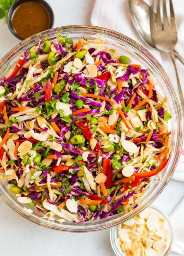 A bowl of Asian cabbage slaw with almonds and ginger peanut dressing
