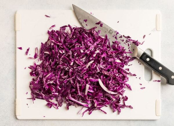A chopped vegetable on a cutting board with a chef's knife