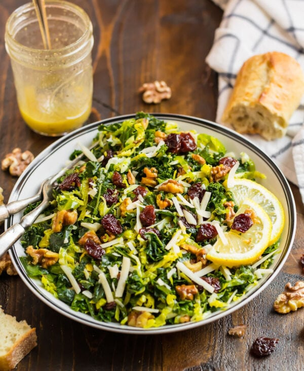 kale and brussels sprouts salad mixed in a bowl with Parmesan, cherries, and walnuts
