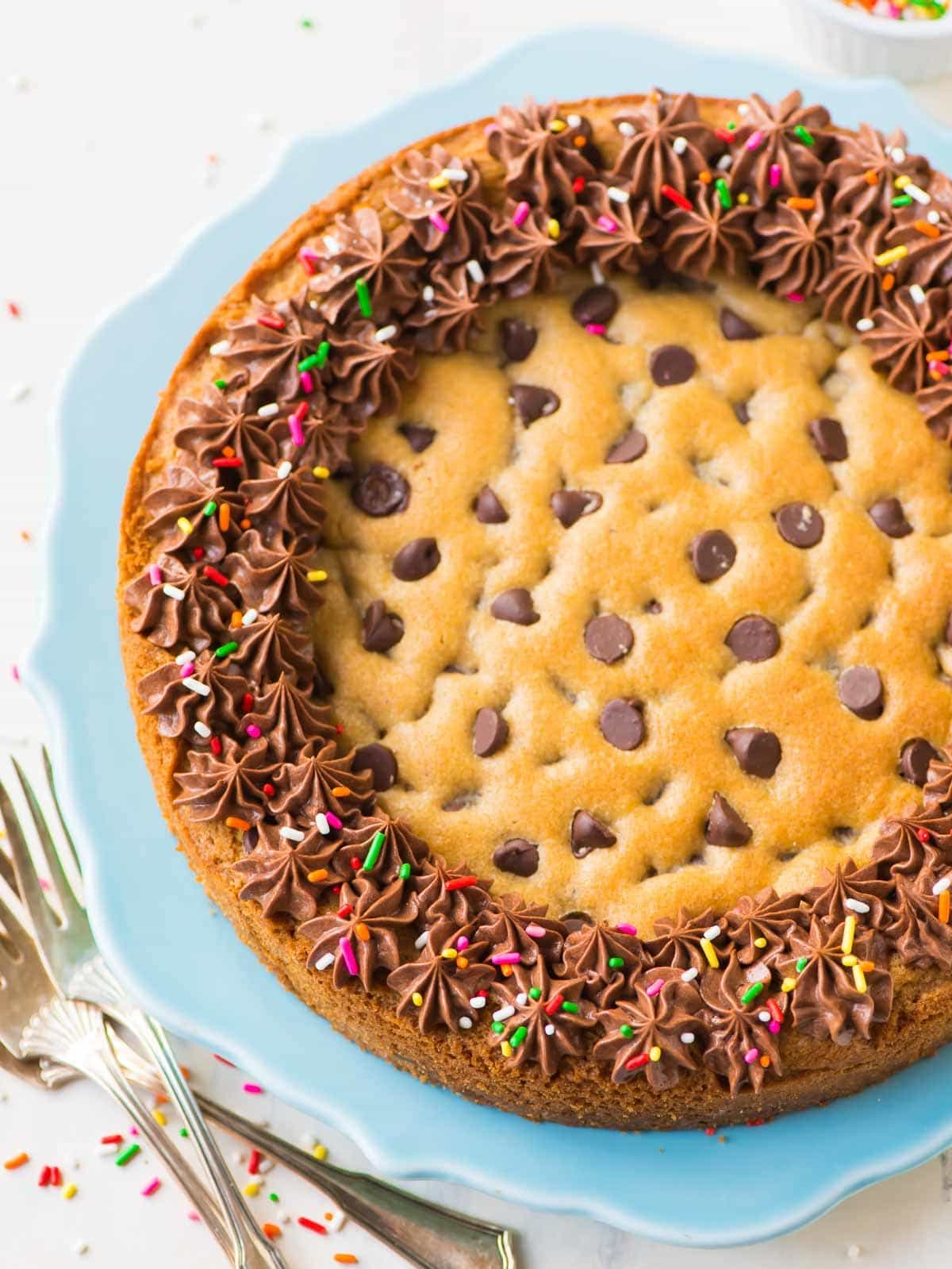 A beautifully decorated chocolate chip cookie cake on a blue plate