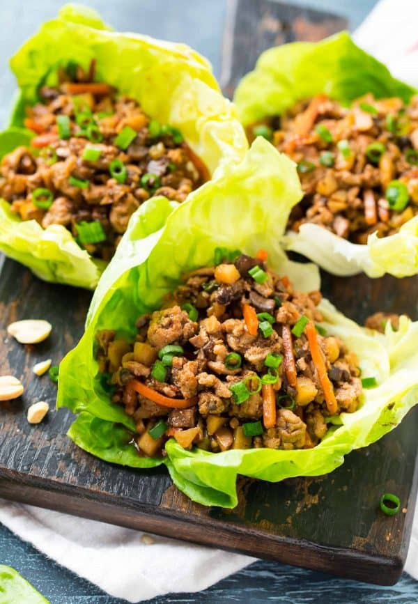 Three lettuce cups filled with ground meat, veggies, and an Asian sauce