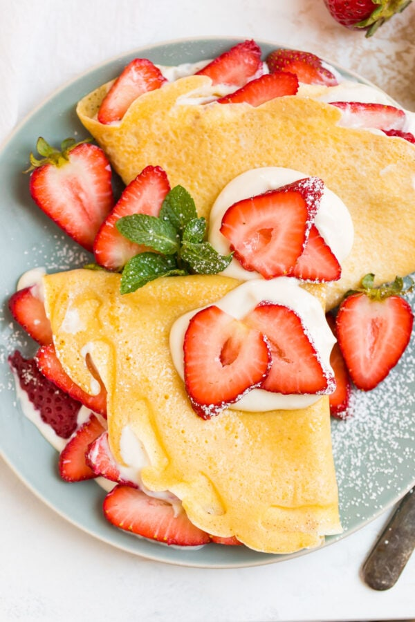 Two strawberry crepes on a light blue plate with strawberries on top