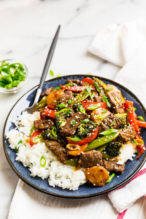 Beef teriyaki stir fry with vegetables on a blue plate with rice