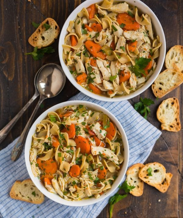 Two white bowls with healthy Instant Pot chicken noodle soup