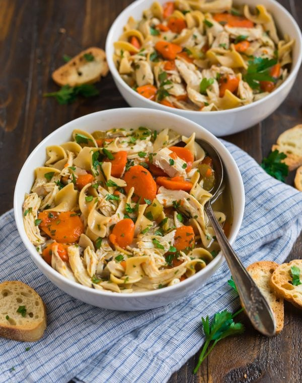 Two white bowls with easy Instant Pot chicken noodle soup