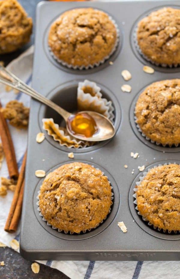 Easy applesauce muffins in a muffin pan and a spoon with honey