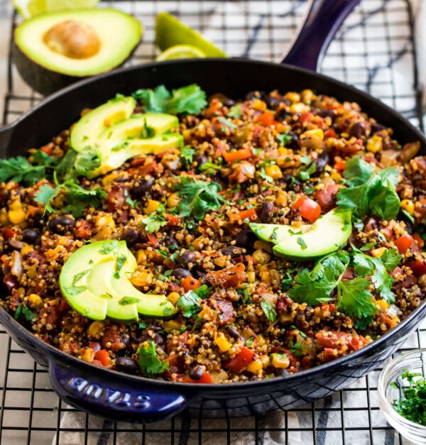 Cooked Mexican quinoa in a skillet with avocado and cilantro