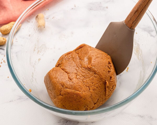 A ball of peanut butter cookie dough in a mixing bowl with a spatula