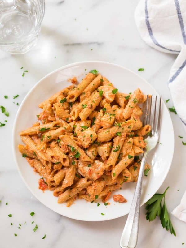 Healthy penne alla vodka on a white plate with chicken