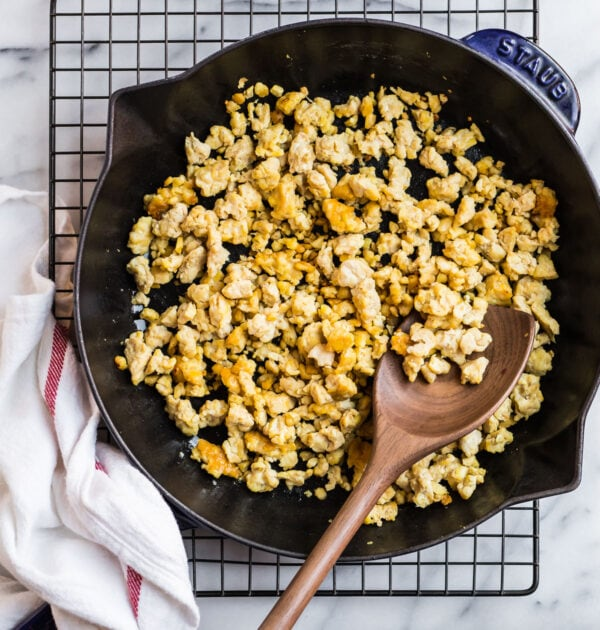 cooked tempeh in a skillet with a wooden spoon