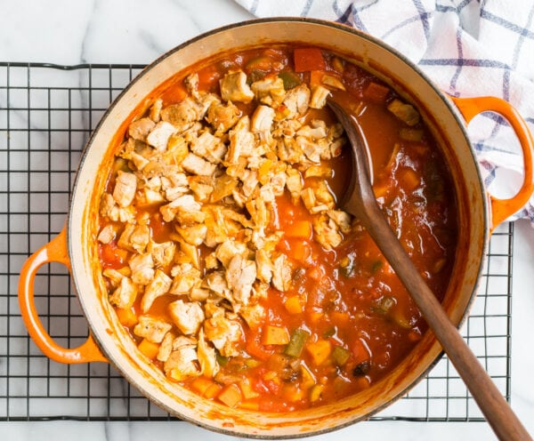 A dutch oven with chicken and tomatoes for making chicken stew