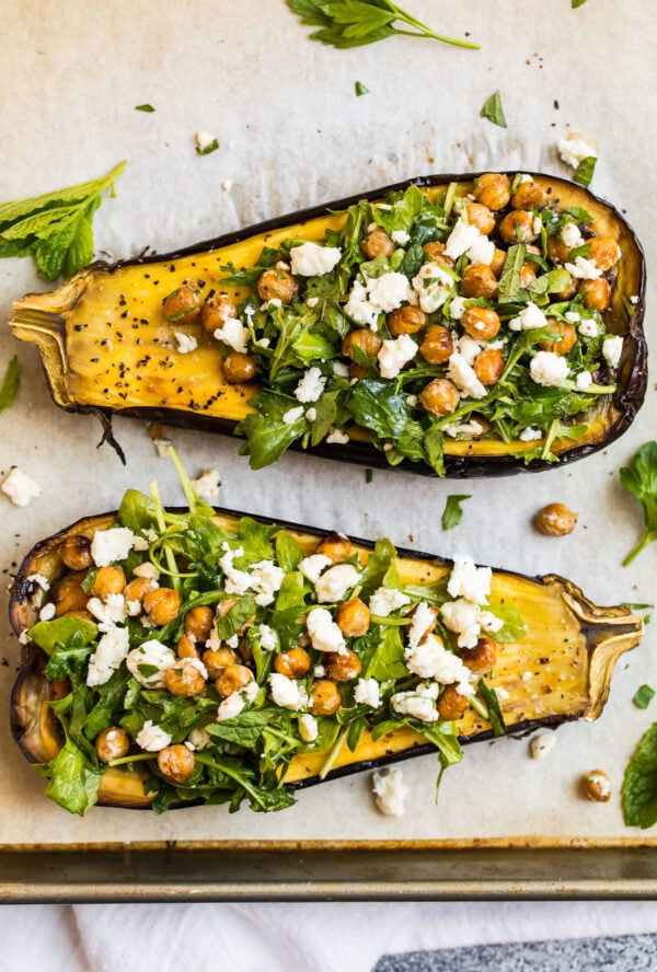 A sheet pan with two roasted eggplant halves topped with a chickpea arugula salad with cheese crumbles
