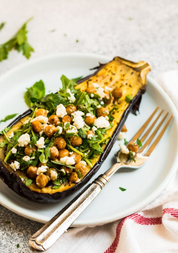 A plate with a roasted eggplant half and chickpea arugula salad